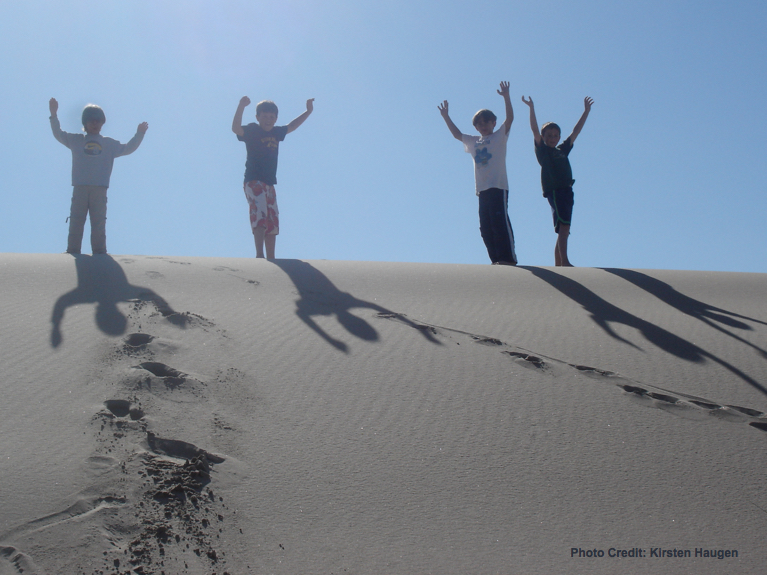 4 boys on top of sand dune