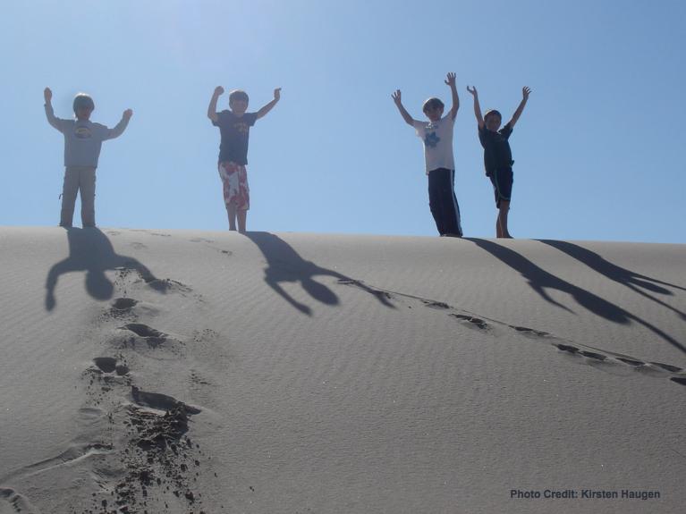 4 boys on top of sand dune