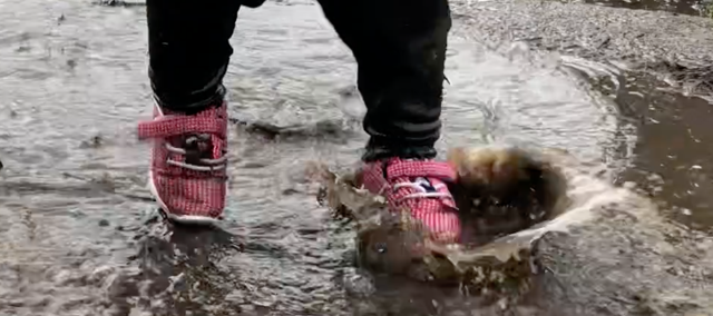 child's feet splashing in mud