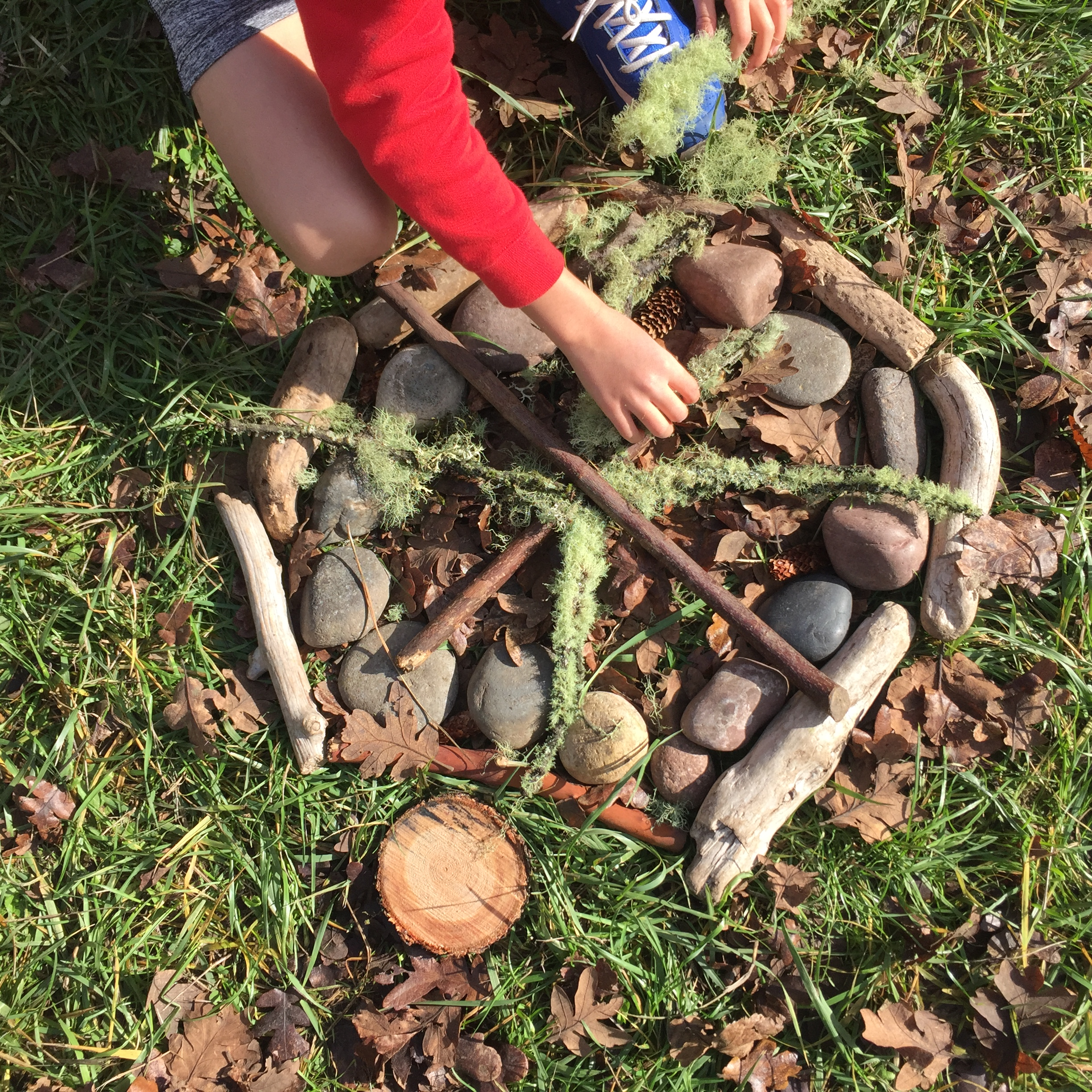 child making art with sticks and leaves
