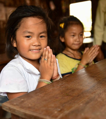 two Lao schoolgirls greeting politely